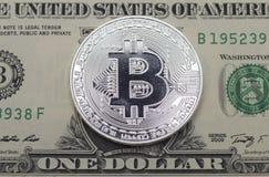 Монетка бита положенная на долларовую банкноту верхней грани одного Стоковое Фото