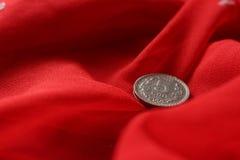 Монетка в красной предпосылке Стоковая Фотография RF