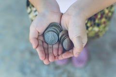 Монетка в руке детей Принципиальная схема дела и финансов Стоковые Фото