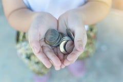 Монетка в руке детей Принципиальная схема дела и финансов Стоковое Изображение RF