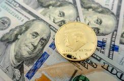 Монетка Дональд Трамп против предпосылки $100 счетов стоковая фотография