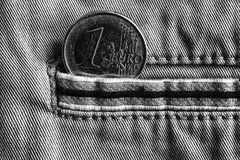 Монетка евро с деноминацией 1 евро в карманн джинсов джинсовой ткани с нашивкой, monochrome съемкой Стоковые Изображения