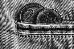 Монетка евро с деноминацией евро 1 и 2 в карманн джинсов джинсовой ткани с нашивкой, monochrome съемкой Стоковое фото RF