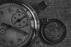 Монетка евро с деноминацией 2 евро и секундомер на фоне джинсовой ткани - предпосылке дела Стоковое Изображение RF
