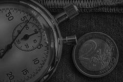 Монетка евро с деноминацией 2 евро и секундомер на worn джинсовой ткани с красным фоном нашивки - предпосылкой дела Стоковое Изображение RF