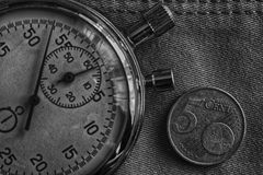 Монетка евро с деноминацией 5 центов евро и секундомера на worn фоне джинсовой ткани - предпосылке дела Стоковые Изображения RF