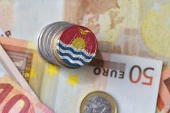 Монетка евро с национальным флагом Кирибати на предпосылке банкнот денег евро Стоковое фото RF