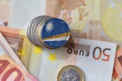 Монетка евро с национальным флагом Маршалловых Островов на предпосылке банкнот денег евро Стоковое Изображение RF