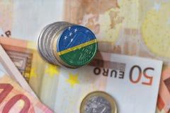 Монетка евро с национальным флагом Соломоновых Островов на предпосылке банкнот денег евро Стоковое фото RF