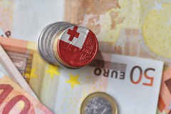 Монетка евро с национальным флагом Тонги на предпосылке банкнот денег евро Стоковые Изображения RF