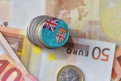 Монетка евро с национальным флагом Фиджи на предпосылке банкнот денег евро Стоковые Фото