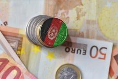 Монетка евро с национальным флагом Афганистана на предпосылке банкнот денег евро Стоковое Изображение