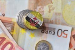 Монетка евро с национальным флагом Бруней Даруссалам на предпосылке банкнот денег евро Стоковая Фотография