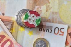 Монетка евро с национальным флагом Бурунди на предпосылке банкнот денег евро Стоковое Изображение RF