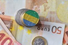 Монетка евро с национальным флагом Габона на предпосылке банкнот денег евро Стоковая Фотография RF