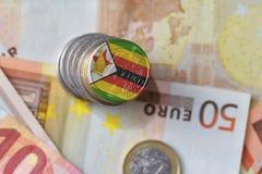 Монетка евро с национальным флагом Зимбабве на предпосылке банкнот денег евро Стоковые Изображения RF