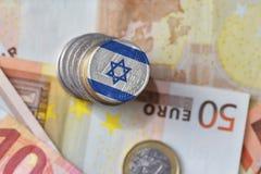 Монетка евро с национальным флагом Израиля на предпосылке банкнот денег евро Стоковая Фотография