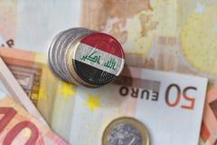 Монетка евро с национальным флагом Ирака на предпосылке банкнот денег евро Стоковые Фото