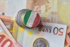 Монетка евро с национальным флагом Италии на предпосылке банкнот денег евро Стоковые Изображения