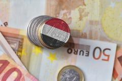 Монетка евро с национальным флагом Йемена на предпосылке банкнот денег евро Стоковые Фото