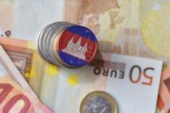 Монетка евро с национальным флагом Камбоджи на предпосылке банкнот денег евро Стоковое фото RF
