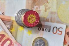 Монетка евро с национальным флагом Кыргызстана на предпосылке банкнот денег евро Стоковая Фотография RF