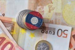 Монетка евро с национальным флагом Лаоса на предпосылке банкнот денег евро Стоковая Фотография
