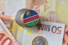 Монетка евро с национальным флагом Намибии на предпосылке банкнот денег евро Стоковые Фото