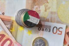 Монетка евро с национальным флагом Судана на предпосылке банкнот денег евро Стоковое Фото