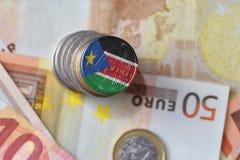 Монетка евро с национальным флагом южного Судана на предпосылке банкнот денег евро Стоковые Изображения