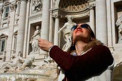 Монетка девушки бросая в известном фонтане Trevi в Риме, Италии Стоковое фото RF
