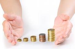 Монетка к деньгам в человеческой руке Стоковое Фото