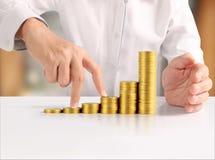 Монетка к деньгам в человеческой руке Стоковые Фото