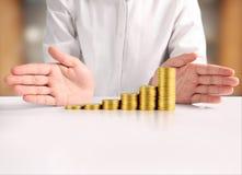 Монетка к деньгам в человеческой руке Стоковая Фотография