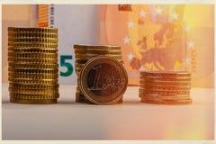 Монетка одного евро и стога сложенных монеток против backgroun Стоковая Фотография RF