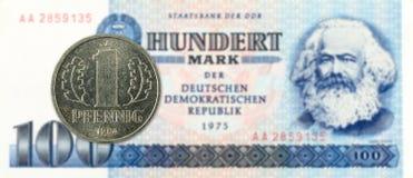 1 монетка пфеннига против исторические 100 восточного - банкнота немецкой метки стоковые изображения rf
