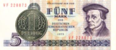 1 монетка пфеннига против исторические 5 восточного - банкнота немецкой метки стоковое фото