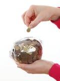 Монетка сбережений руки женщины в белых автожелезнодорожных перевозках Стоковые Фото