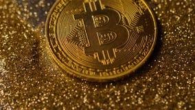 Монетка сделанная системой Bitcoin падает вниз на золотой макрос пыли