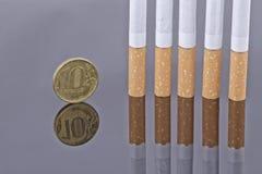 Монетка сигареты и 10 рублевок Стоковое Изображение RF