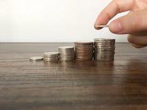 Монетка удерживания руки женщины к штабелировать для сбережений или дело растут вверх концепция стоковые изображения rf