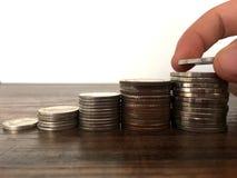 Монетка удерживания руки женщины к штабелировать для сбережений или дело растут вверх концепция стоковое изображение