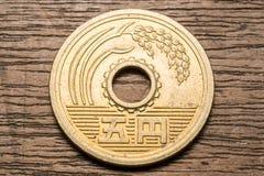 Монетка 5 японских иен на деревянном столе Стоковое Фото