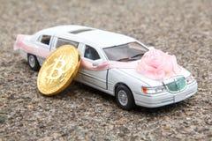 Монетка Bitcoin золотая около модели роскошного белого автомобиля на предпосылке асфальта Стоковые Фотографии RF