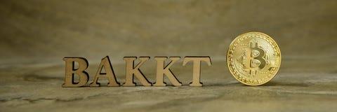 Монетка Bitcoin и рядом с деревянным с BAKKT стоковое фото