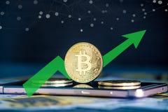 Монетка Bitcoin на экране телефона на предпосылке банкнот евро Зеленая стрелка диаграммы роста цены стоковые изображения rf
