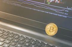 Монетка Bitcoin помещенная на черной тетради Конец-Вверх Bitcoin, обменивает виртуальное значение, секретные цифровые деньги Живо стоковые фотографии rf