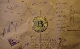 Монетка bitcoin против предпосылки скомканной бумаги с диаграммами Стоковые Изображения RF