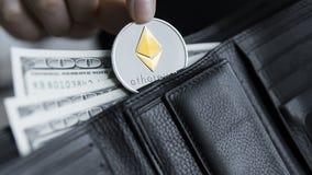 Монетка Ethereum и 100 долларов счетов в кожаном бумажнике Ethereum с долларом в портмоне Выгода от минировать секретный Стоковые Фото