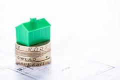 Монетки английского фунта покупая новый дом Стоковые Изображения